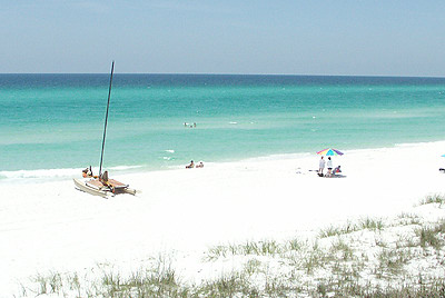 The Emerald Coast Beach with catamaran and beach umbrella